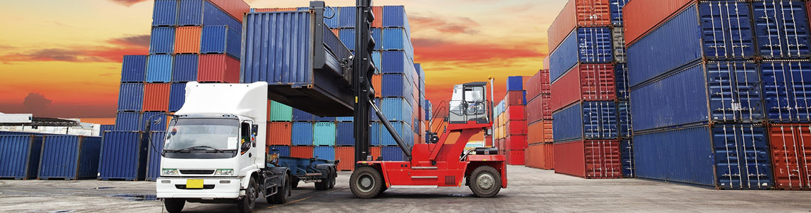 Forklift loading container on transport truck